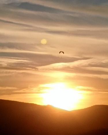 Vuela en parapente en la puesta de sol
